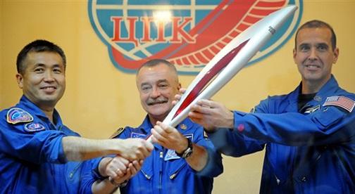 Le Japonais K. Wataka, le Russe M. Tiourine et l'Américain R. Mastracchio posent une dernière fois en compagnie de la torche olympique très stylisée, avant de rejoindre l'ISS. (Crédit photo : AFP)