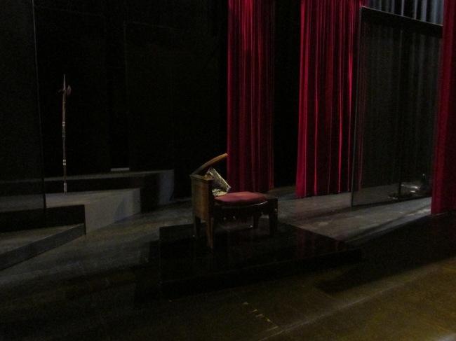 La scène de la salle Pierre Brasseur. Minimaliste en décor, avec le fauteuil à moitié détruit du roi Bérenger Ier, incarné par Michel Bouquet. (Crédit Photo : Camille Degano)