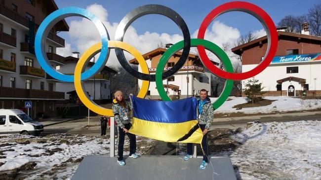 Bogdana Matsotska et son père posent devant les anneaux olympiques avec le drapeau ukrainien (Crédit photo : D.R.)