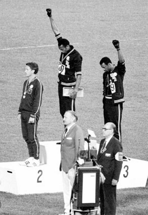 Tommie Smith et John Carlos, sur le podium du 200m à Mexico en 1968, lèvent leur poing ganté de noir. (Crédit Photo : D.R.)