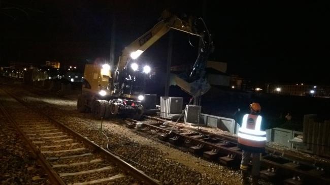 Sous les ordres du chef de chantier, la pelle soulève les rails (Crédit photo: Erwan Schiex)