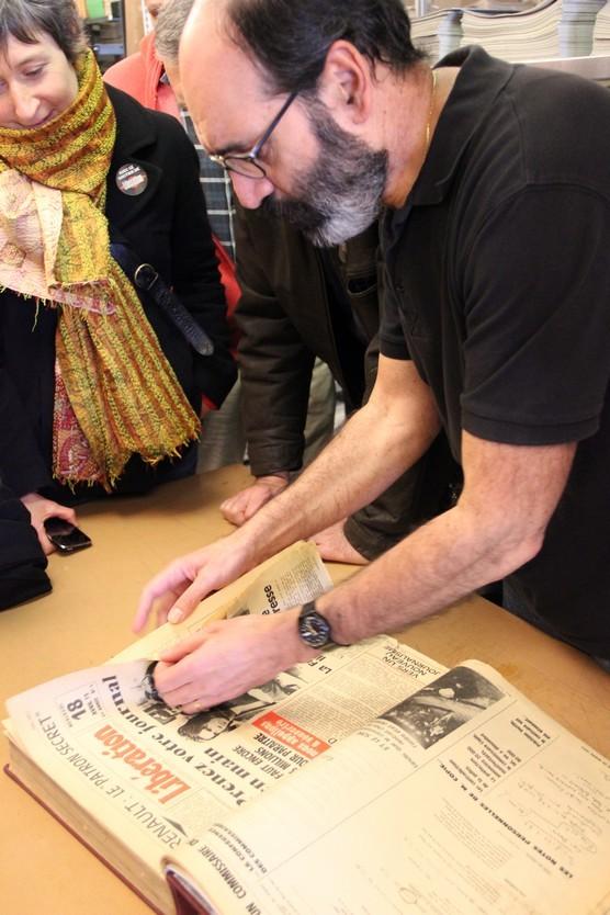 Alain Brillon, archiviste et dessinateur pour Libération, feuillette les pages du tout premier numéro du journal. Il raconte son histoire aux visiteurs. (Crédit photo : E.Patricio)