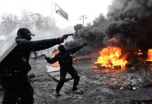 Scène d'affrontement à Kiev, où un manifestant brandit une arme à feu, le 22 janvier 2014. (crédit photo : Vasily Maximov)