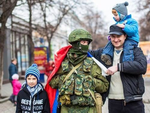 Une famille posant avec un militaire russe en Crimée (crédit photo : Dr)