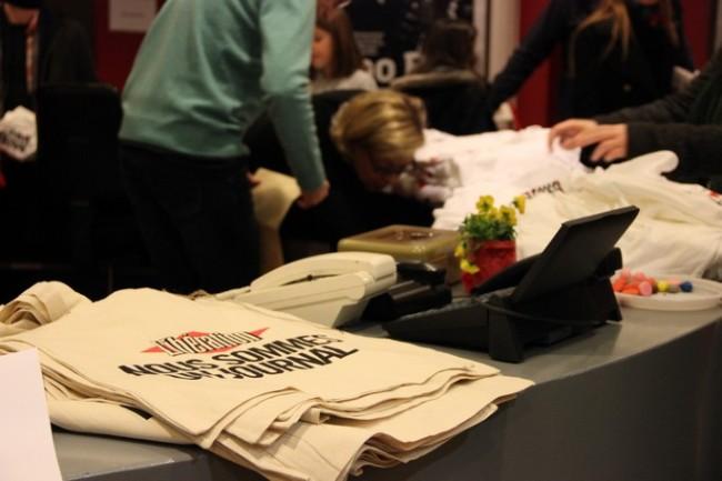 A l'entrée du bâtiment, des tee-shirts à « l'effigie » de Libé dessinés par Jean-Paul Gauthier, des sacs « Nous sommes un journal » et d'autres babioles sont vendues aux visiteurs. (Crédit photo : E.Patricio)