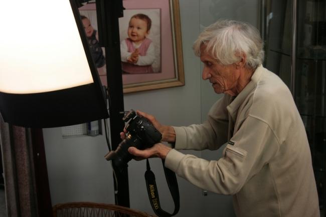 Georges Martin photographie un client dans son studio. (Crédit Photo : Nicolas Richen)