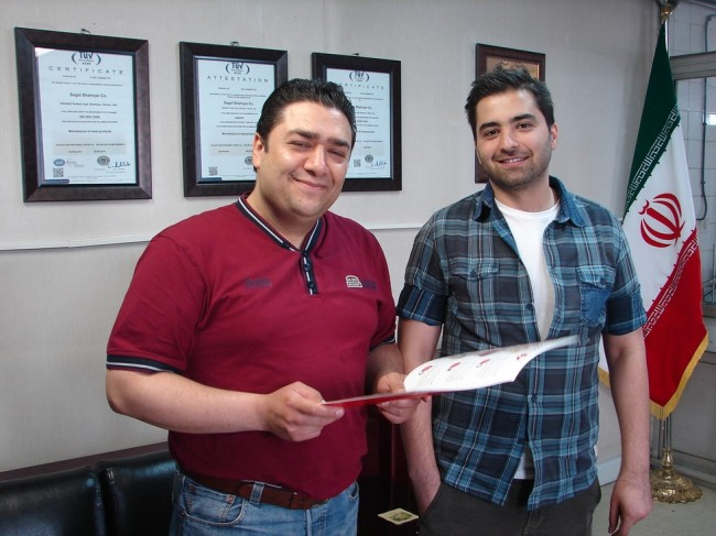 Mohsen Haji Abedini et Amir Hosein Mazandarani, les deux responsables des ventes, posent fièrement devant trois des certificats sanitaires de l'entreprise. (Crédits : S.Shojaei)