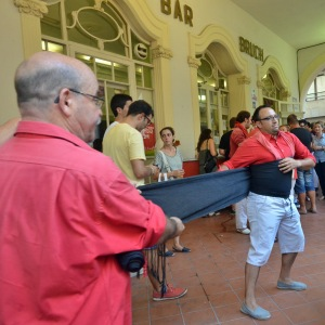 Les castellers s'entraident pour attacher la faixa castellera. (Crédit photo : Manon Bazerque)