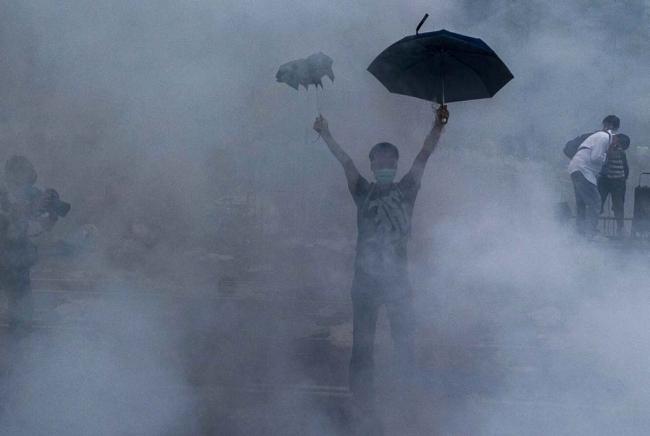 Un manifestant se protège des gaz lacrymogènes en ouvrant ses deux parapluies. (Crédit photo : Xaume Olleros/AFP)