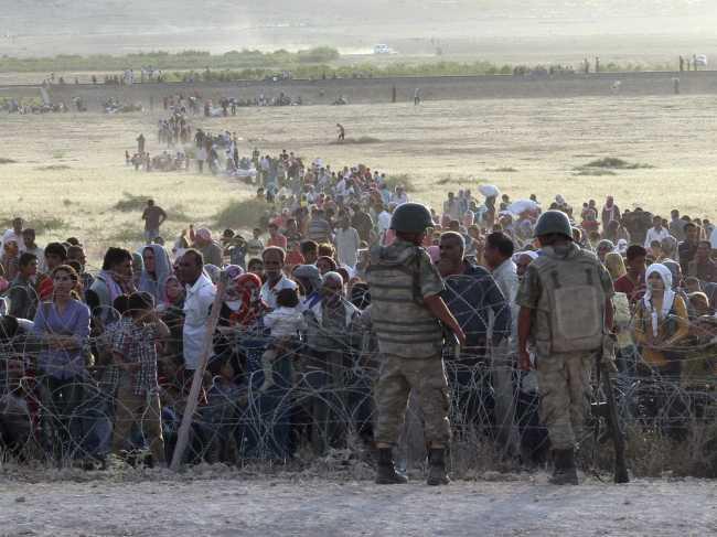 Des soldats turcs regardent une colonne de réfugiés syriens en provenance de Kobané, près de Suruc. Crédits: Reuters