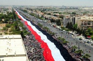 Manifestation pro Assad en 2011, au début du conflit syrien. La bande rouge du drapeau, symbolisant le socialisme arabe, est remplacée dans le drapeau des rebelles par la bande verte, représentant l'Islam. Crédit photos : D.R.