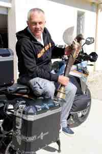 Jean-Pierre Goy et son trophée de meilleur cascadeur mondial, sur une de ses motos. (Crédits : Eloïsa Patricio)