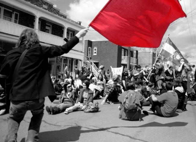 Un étudiant fait flotter un drapeau rouge, la couleur symbolisant le soulèvement des « carrés rouges », lors d'un sit-in à Saint-Jérôme (Laurentides), une petite ville au nord de Montréal. (Archive avril 2012 / Crédit Photo : Nicolas Richen)