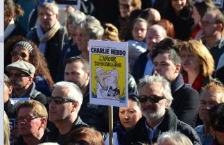 """Des Unes de Charlie Hebdo brandies par la foule. Celle-ci est caractéristique de ce dimanche de rassemblement à travers la France : """"L'amour plus fort que la haine"""". (Crédit photo : Jérémy Satis)"""