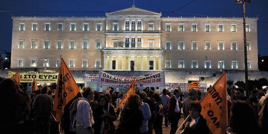 Des manifestants devant le parlement grec lors du vote des lois anti-austérité. Crédit : Louisa Gouliamaki AFP