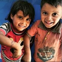 Ces deux enfants ont demandé au photographe de leur dessiner une montre et une voiture. Ils vivent au camp de Roj, situé en Syrie. (Crédit photo : Instagram/@alanali1990)