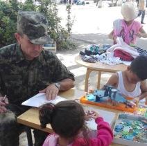 Un militaire serbe tient compagnie aux enfants, réfugiés de Syrie, Irak et Afghanistan. Le ministre de l'Education et l'armée serbe apportent tentes, crayons et livres de coloriage pour aider les migrants qui stationnent à Belgrade. (Crédit photo : Instagram/@oxanachelysheva)