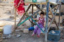 Une petite fille s'est fabriqué une balançoire à l'aide d'une corde, d'un bout de carton et d'une couverture. Elle se balance au milieu des débris. (Crédit photo : Matthias Somm)