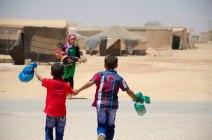 Deux enfants courent vers leur grande soeur après avoir reçu des cadeaux lors d'une distribution organisée par une ONG locale. (Crédit photo : Matthias Somm)