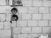 Deux petites filles se cachent lorsque nous sortons de la voiture, devant la tente de leurs parents. (Crédit photo : Matthias Somm)