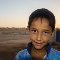 Un enfant joue parmi les débris en fin de journée, après la chaleur. (Crédit photo : Matthias Somm)