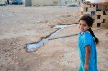 Une petite fille adresse de larges sourires à des membres d'une ONG venus apporter leur aide au village. (Crédit photo : Matthias Somm)
