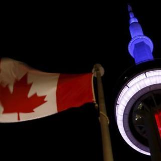 Au Canada, la CN Tower est illuminée en bleu-blanc-rouge (crédits photo : Chris Helgren/Reuters)