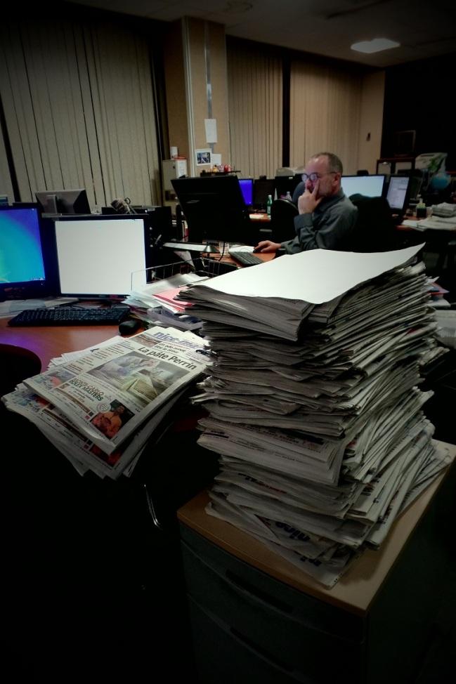 Pile de journaux sur les bureaux des journalistes qui apportent les dernières touches à l'édition du 27 février 2016. Crédit photo Elsa Hellemans