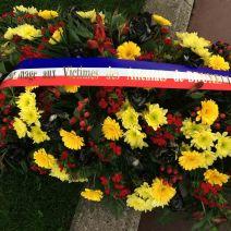 Après avoir joué la sonnerie aux morts, cette gerbe de fleurs a été déposée près du monument aux morts. (Crédit: Thomas Woloch)