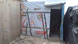 Des abris de fortune faits de planches de bois et de bâches décorées de graffitis abritent les migrants (Crédit photo : John Brewer).