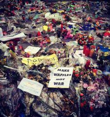 Plusieurs jours après l'attentat ayant touché l'aéroport de Bruxelles et tué 32 personnes, les passants se recueillent dans la ville en déposant des fleurs, des bougies ou encore des pancartes. (Crédit : Instagram @MarieTeaEliza)