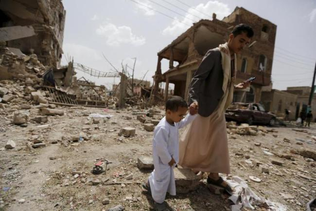 A man and a boy walk at a site hit by a Saudi-led air strike in Yemen's capital
