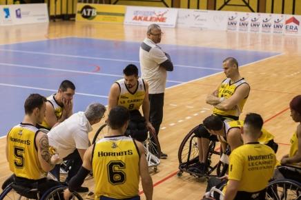 L'entraîneur, Daniel Paquet, donne ses instructions aux joueurs pendant un quart-temps.