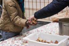 Un des bénévoles donne du pain et de la soupe à un migrant. (Crédit photo : Gaspard Flamand)