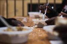Autour d'une table en bois, les migrants prennent un petit-déjeuner. (Gaspard Flamand)